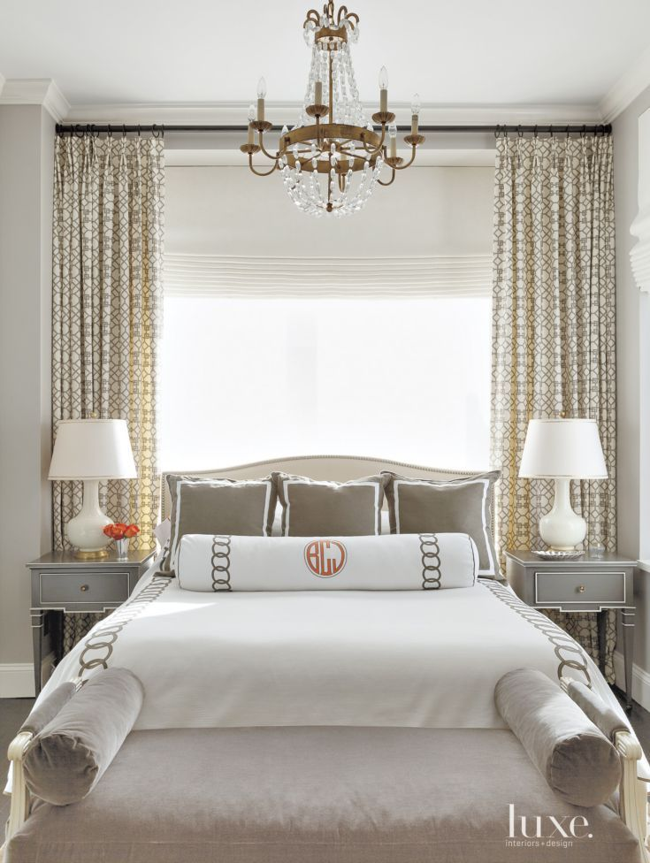 In the master bedroom, custom bedding from Leontine Linens in New Orleans—in white piqué with a charcoal linen appliqué—sets a refined tone. The Hickory Chair bench is upholstered in charcoal velvet. Custom curtains made of a Kravet fabric add an interesting pattern. Gourd ceramic lamps by Festoni sit atop side tables by Vanguard Furniture.