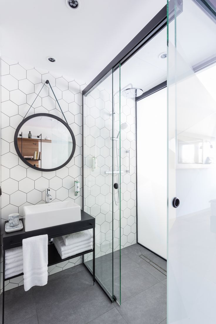 master bathroom white hexagon wall tile with dark grout framed glass shower round wall mirror slim design vanity and sink