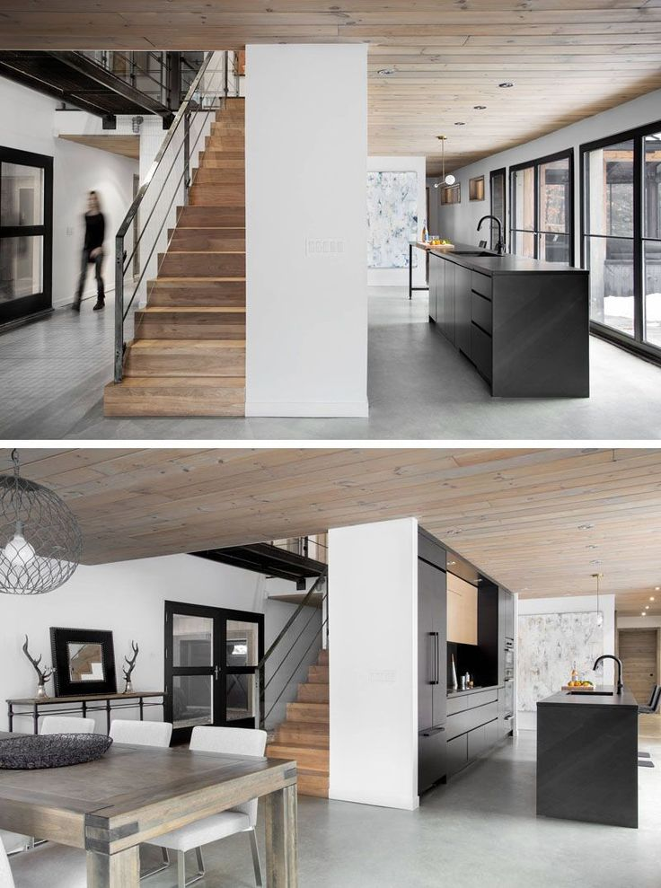 This modern black kitchen stands out against the light floors and white walls, as well as the stairs, and fits right in with all of the other black elements found in the home.