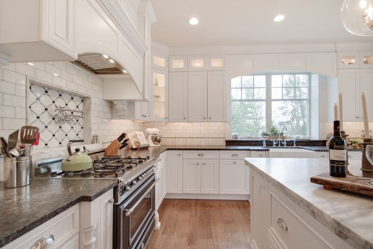 This bright white kitchen features a Mont Blanc honed quartzite island countertop with a Silver Pearl Leathered granite countertop perimeter. The backsplash has New Calacatta marble subway tile with a beautiful waterjet mosaic insert over the stove. Kitchen by Stoneshop from Cherry Hill, NJ.