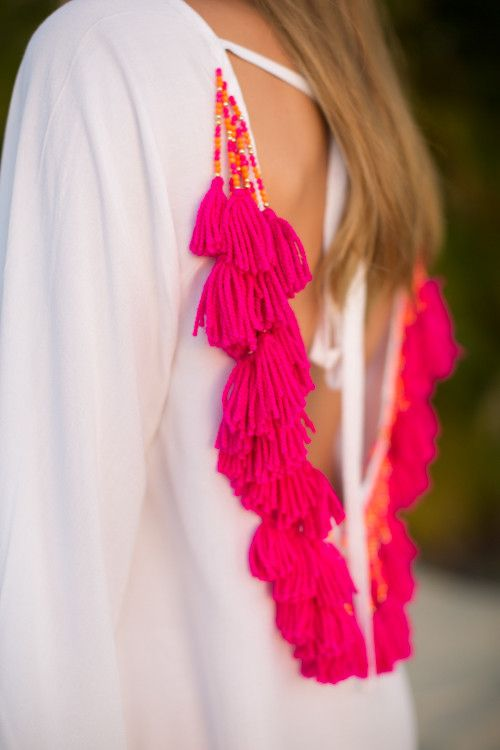 How gorgeous is a white sundress with bold colored tassels and beads?! This…