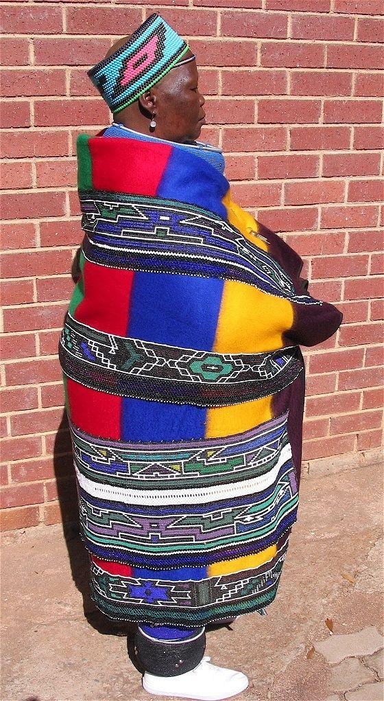 Africa | Ndebele doll maker, Sophie Mosombuka,  wearing her elaborate beaded blanket.  | ©Val Hearder