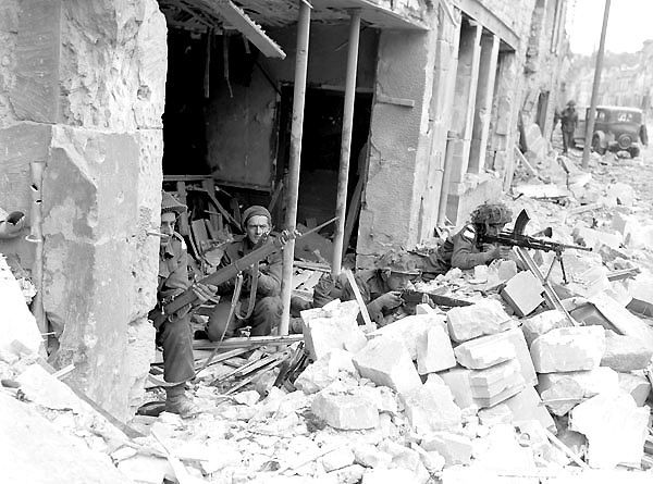 Canadians capture Caen - Personnel of the Regina Rifles in ruined storefront, Caen, France, 10 July 1944.