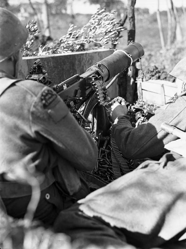 An unidentified gunner of the Saskatoon Light Infantry (M.G.) laying down harassing fire with a Vickers machine gun near Ortona, Italy, 7 January 1944.