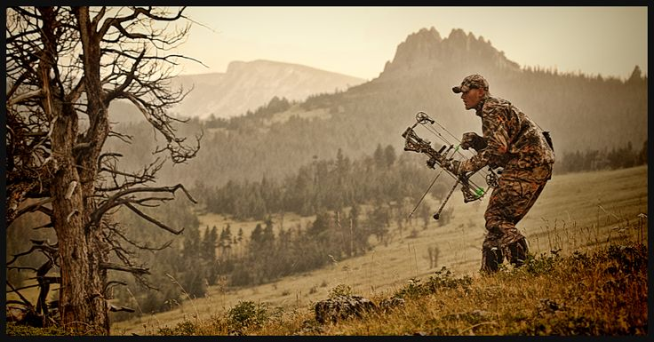 archery hunter stalks mountainside montana with bow and arrow