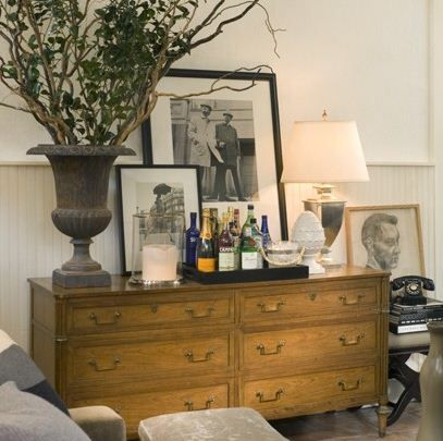 David Jiminez.  Love the low dresser as bar and artful arrangement of photographs, urn and lamp.