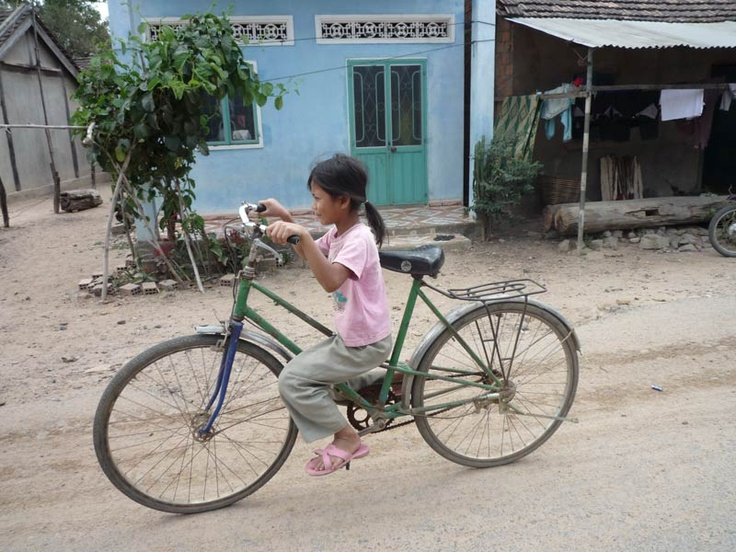 Local girl cycles the family bike in Ba Nah village, Kon Tum, Central Vietnam