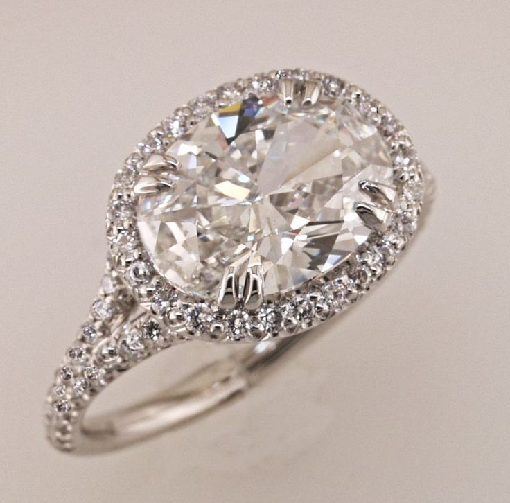 Oval diamond ring set east-west with a halo and a split shank.
