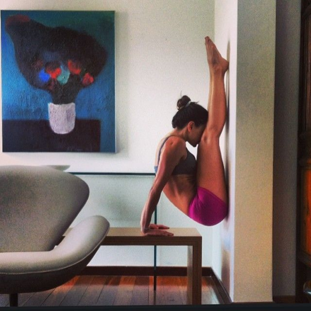 Healthy life style indoor yoga Strength and flexibility combined in this forward bend on the wall.