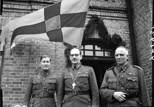 Kenttäpiispa kahden sotilaspastorin seurassa, KTR 3 kasarmi, Riihimäki 17.4.1943. SA-kuva-arkisto.