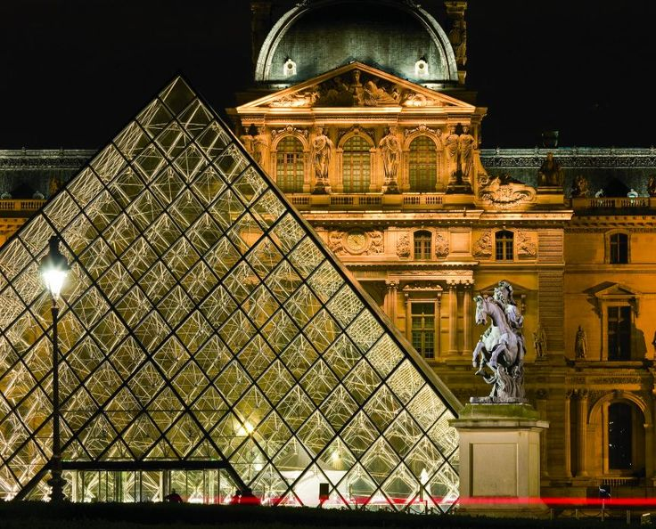 After closing hours, floodlights illuminate the Louvre Museum, its famous glass pyramid, and a marble statue of King Louis XIV atop his trusty steed.