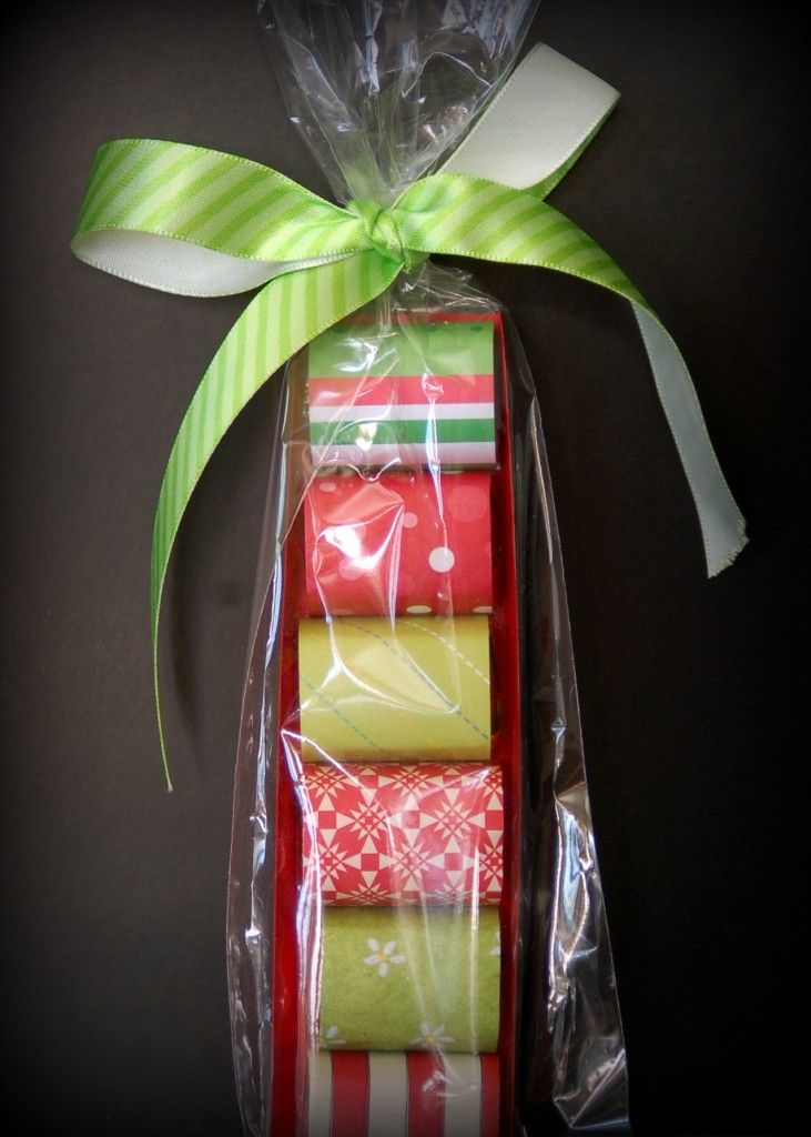 A tray (made of card stock) of candy miniatures (wrapped in decorative scrapbook paper) wrapped in a cellophane pretzel bag and tied with a bow.