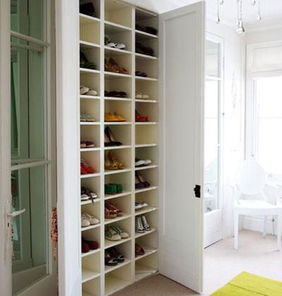 This floor-to-ceiling shoe shelf hides neatly behind double doors. The white shelves reflect light into the dark cubbies, making every pair easy to see.   Photo: Antony Crolla   myhomeideas.com