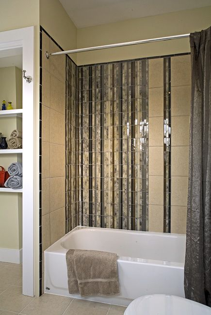we created a waterfall effect above this bath with glass tile black iridescent glass tile