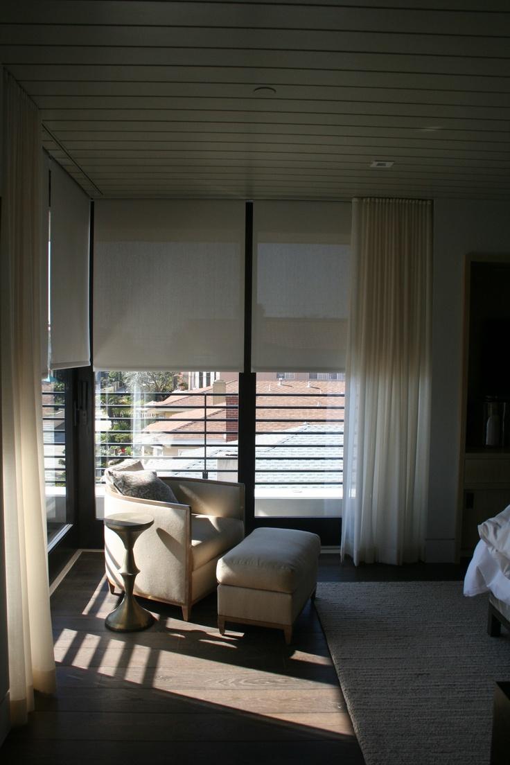Estores enrollables motorizados combinados con cortinas en el dormitorio. Fuente: bayscreens.net