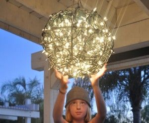 Reuse 2 flower baskets frames, black pipe cleaners, and white holiday lights, and turn them into a beautiful outdoor glowing chandelier!