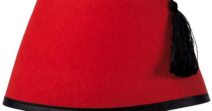 Quem usa chapéu Fez vermelho. Fez é um chapéu em forma de cone com a ponta amassada. Originou-se no Marrocos e tornou-se mais popular durante o Império Otomano, que hoje é a Turquia. Um Fez também pode ter um turbante em torno dele.