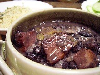 フェジョン(ブラジルの豆シチュー) ブラジルの食卓にはかかせないお袋の味、フェジョン。ご飯にかけていただきます。家庭によって、色々な作り方がありますが、私の作るものは、基本的にベーコン入り(コン・ベーコン)です。これは、ブラジルに滞在していた人にも褒められたレシピです。 mariajinha 材料 カリオカ豆(又はフェジョン・プレット。日本では、うずら豆で代用可) 300g ニンニク 1カケ ベーコン(ブロック) 100~150g 玉ねぎ 1個 セロリ 茎1本分 オリーブオイル 大さじ1~2 塩 適宜 ローリエ(あれば) 1~2枚 作り方 1 豆は12時間以上水に浸しておく。 2 ニンニク、玉ねぎ、セロリはみじん切り、ベーコン(ブロック)は、1.5~2cm程度の角切りにする。 3 鍋に豆とローリエ(あれば)と水を入れ灰汁を取りながらやわらかくなるまで煮る。(水が少なくなったら足す)*圧力鍋の場合は、ヒタヒタより少し多めの水量で強火にかけ、灰汁をとり、蓋をして圧がかかったら弱火にして2~3分で火をとめ自然減圧。 4…