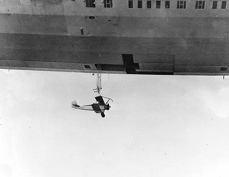 N2Y-1 training plane beneath trapeze and T-shaped opening of the hangar deck of the airship USS Akron