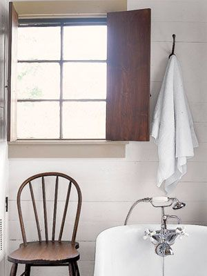 Rustic wood shutters give early-American appeal to a New England bathroom.