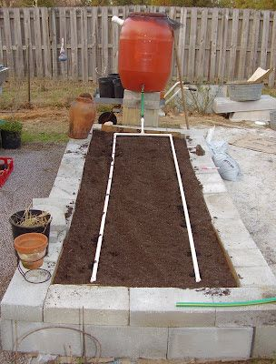 """The second drip irrigation barrel was easier and less expensive to make.   I drilled a 7/8"""" hole near the bottom and forced an old ¾"""" hose b..."""