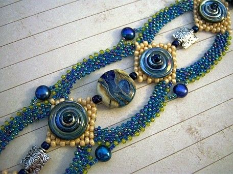 Metallic Blue Disk - This bracelet is worked in peyote stitch around a large glass focal bead and 2 sterling silver beads. It has 4 large disc beads in metallic blue on 4 center panels of peyote stitched seed beads in a creamy shell color. It is accented by 4 dark blue freshwater pearls.
