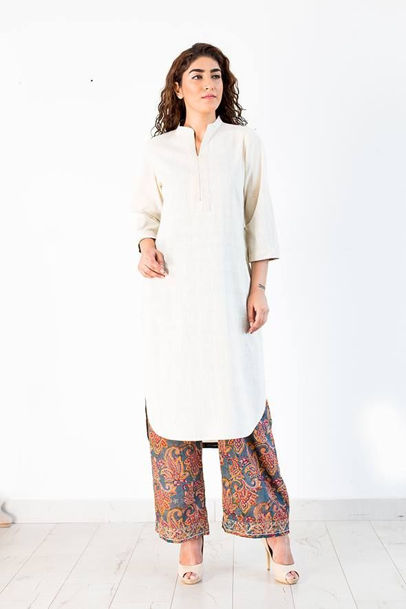 A straight cut long kurta with uneven hemline in front and back , back hem is slightly longer than front , beautifully crafted with tucks details on neckline and sleeve hem and contrasting hand block printed fabric pipping details at sleeve , neck and side slits . This kurta when paired with hand embroidered farshi pants ( as shown in pic ) is perfect for your office meetings or an evening dinner ! The texture of the hand spun and hand woven Khadi fabric adds to the rich look ! 100 % khadi
