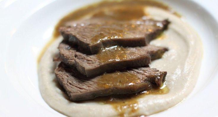 Lavare e mondare le verdure, poi tagliarle a pezzetti e rosolarle in una pentola dai bordi alti con un filo di olio extravergine. Aggiungere il pezzo di carne...