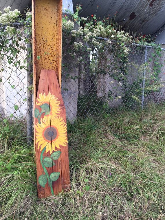 This vintage ironing board has been reclaimed, and is now a beautiful piece of art. A hand painted sunflower scene was added to the top of the