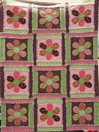 Made with rough-edge applique flowers. Used flannel instead of batting for this quilt - she said she cut up an old flannel sheet for the batting.