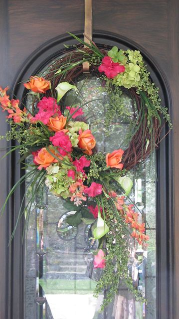 Spring wreath including pinks, oranges and greens on a grape vine wreath. Perfect piece to hang on your front door and welcome your guests.
