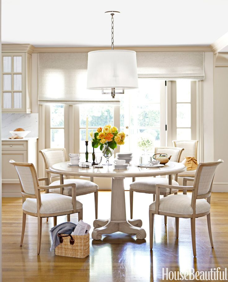 In the breakfast area of a Corona del Mar house designed by Barbara Barry, Conrad window shades filter the light. A Barbara Barry Westport chandelier for Visual Comfort hangs above a Stuart table by Richard Mulligan. Barry had the homeowners' black chairs painted and reupholstered in linen.  Victoria Pearson  - HouseBeautiful.com