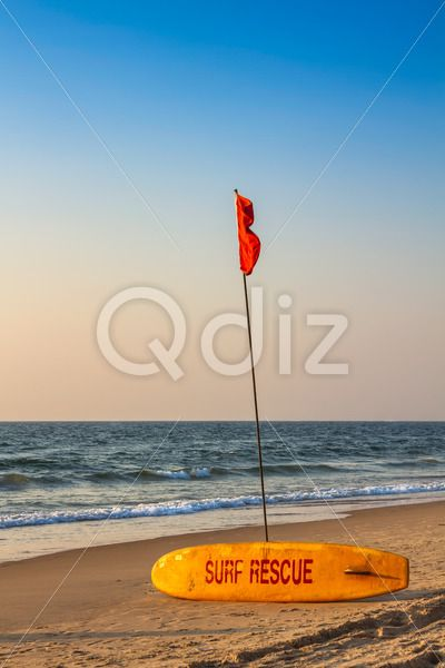 Qdiz Stock Photos | Rescue surfboard on sand beach with flag,  #assistance #beach #board #bodyboarding #bodysurfing #coast #coastline #danger #devon #emergencysign #equipment #flag #guard #life-saving #lifeguard #lifesaver #lifesaving #ocean #outdoors #protection #red #rescue #risk #safety #sand #saver #sea #security #shore #sky #sos #summer #surf #surfboard #surfing #survival #vacation #warningsign #water #yellow