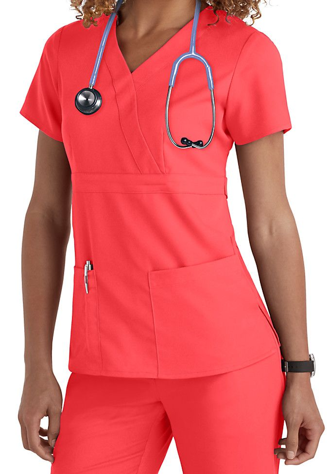 No matter your caregiving profession, we think you'll love this Grey's Anatomy 3-pocket mock-wrap scrub top especially in the vibrant Papaya color! | Scrubs & Beyond