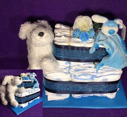 Chique luiertaart jongen voor een baby shower. De taart is mooi gedecoreerd met luxe linten, strass banden en een mooi strik. Met een tutpop voor de kleine