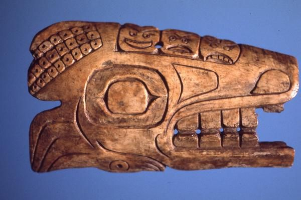 Bone shamanistic charm carved in image of sea lion, and possibly octopus.