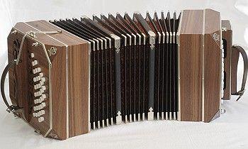 BANDONEÓN Es un instrumento musical de viento, libre, a fuelle, pariente de la concertina, de forma rectangular, sección cuadrada y timbre particular.