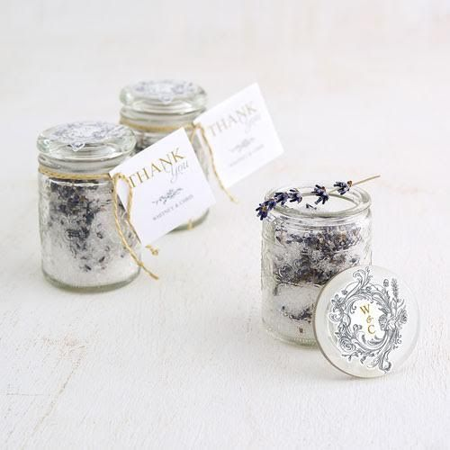 Pressed glass floral decorated mason jar wedding favors with glass stopper. A fresh take on the traditional mason jar that makes a statement. Features a beautiful embossed vintage inspired floral pattern. Add a personalized tag or sticker for the perfect finishing touch. Available from Madeline's Weddings - as seen on www.BrendasWeddingBlog.com