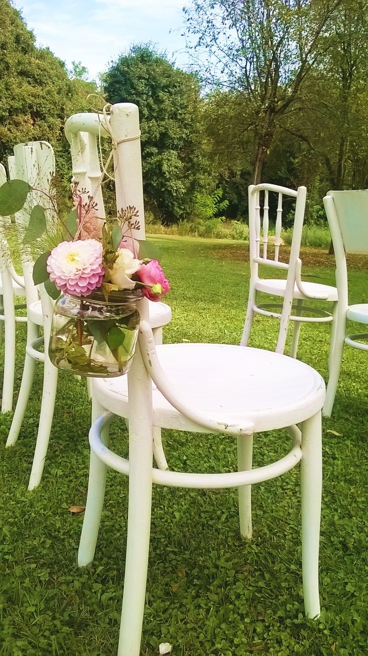Wedding in the garden. White chairs with flower decor for the ceremony