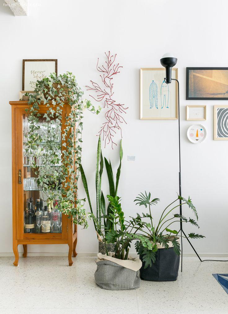 detalhe de uma sala de estar com parede de quadros, plantas e cristaleira antiga - matéria em parceria com a https://boobam.com.br/