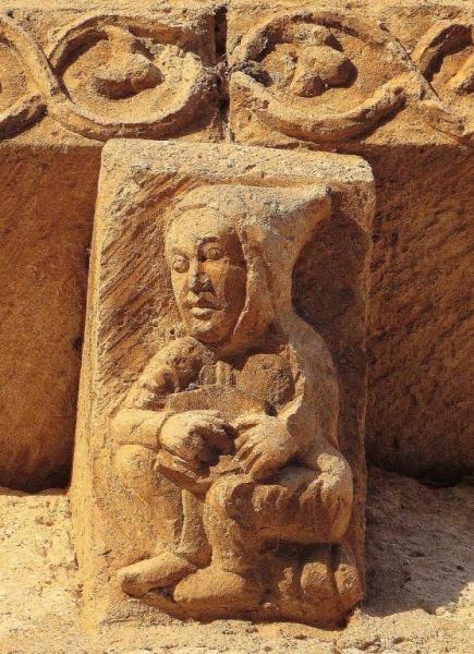 Monje con libro, iconografía románica - Canecillo del ábside de la iglesia de San Cipriano, Oquillas, Románico del Esgueva (Burgos)
