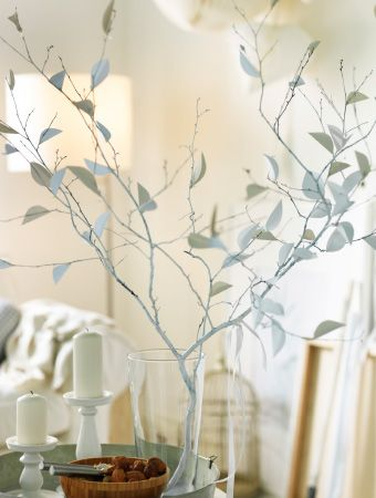 A white painted tree branch with handmade leaves placed in a glass jug on a metal tray with white candles in white candlesticks.