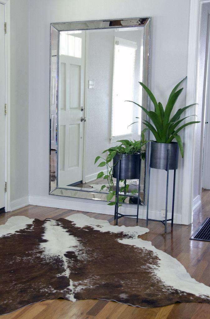 espejo grande plateado alfombra de piel d toro, macetas negras