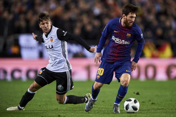 Lionel Messi of FC Barcelona is challenged by Luciano Vietto of Valencia CF during the Copa de Rey semi-final second leg match between Valencia and Barcelona on February 8, 2018 in Valencia, Spain.