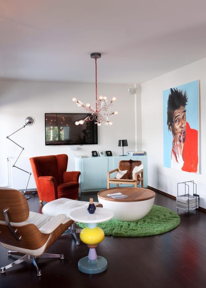 SOFALØS STUE: Stuen er innredet med en uvanlig møbelmiks: Eames Lounge Chair fra Vitra, Shuffle sidebord fra Andtradition, bord med oppbevaringsplass fra Bolia, en gammel ørelappstol og en enkel hvilestol fra R.O.O.M. kledd med kuskinn fra Ikea. Gulvteppet er fra Permafrost, taklampen fra Ingo Maurer. Bildet er malt av Kristoffer Evang. Flatskjermen er nesten borte i vrimmelen.