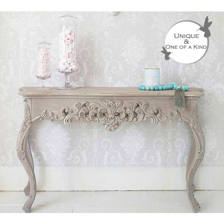 Grace Shabby Chic Console Table - This classic shabby chic console table has an alluring and evocative design carved from wood. It has been heavily distressed to give an antique patina in the palest shade of grey with a white undercoat.