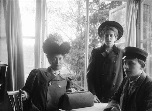 Gruppbild. Kvinna och två barn iklädda ytterkläder framför fönster. Interiör