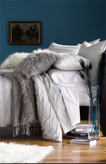 From the wall color to the faux fur pillows, love everything about the look of this room.
