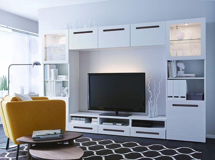 Séjour avec une grande combinaison média et divertissement, composée d'un banc TV blanc, d'étagères avec des portes en verre dépoli et de portes et faces de tiroirs en blanc brillant