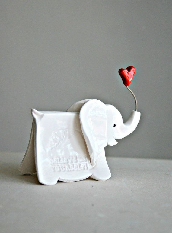 Small white elephant sculpture with imprinted word Bloom on one side and Believe in yourself on other side of elephant.    Hand built in ceramics